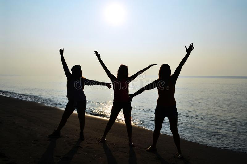 Silhouette of 3 ladies with sunrise on the beach. Silhuette of three ladies having fun with sunrise on the beach stock photo
