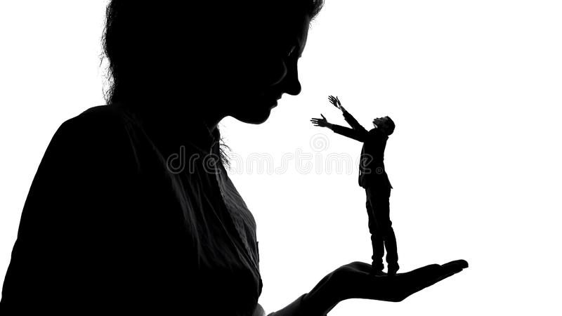 Silhouette of lady holding tiny male admirer in hand, women power, domination royalty free stock photo