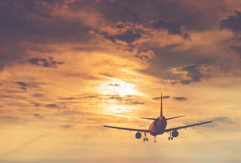 Silhouette of landing airplane at dawn. Conceptual image symbolizing travel industry stock image