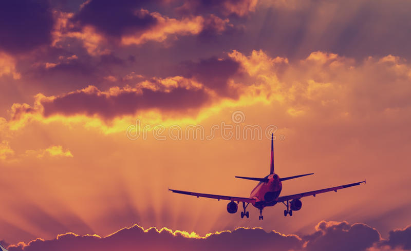 Silhouette of landing airplane at dawn. Conceptual image symbolizing travel industry stock photography