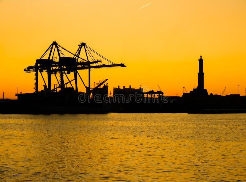 Silhouette of Lanterna lighhouse of city of Genoa Genova, the symbol of the city, in the port at sunset. Italy stock image