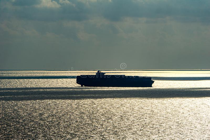 Silhouette of large container ship anchors in the sea stock images