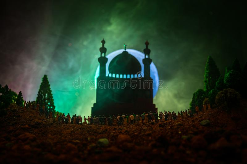 Silhouette of a large crowd of people in forest at night standing against a blurred mosque building with toned light beams on fogg stock photo