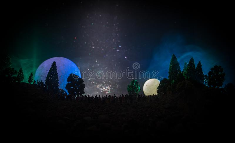Silhouette of a large crowd of people in forest at night watching at rising big full Moon. Decorated background with night sky wit royalty free stock photography