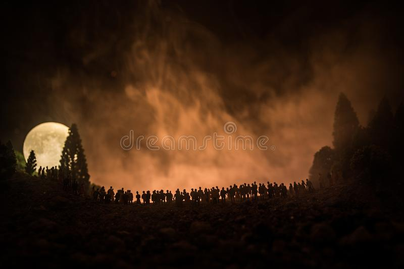 Silhouette of a large crowd of people in forest at night watching at rising big full Moon. Decorated background with night sky wit royalty free stock photos