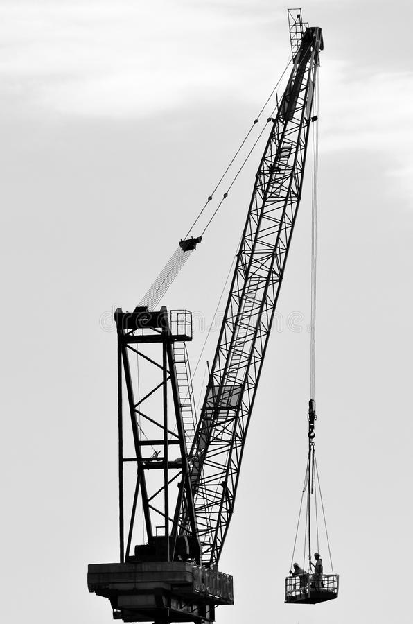 Silhouette of a large tower crane lifting construction workers. Construction concept with copy space (BW royalty free stock images