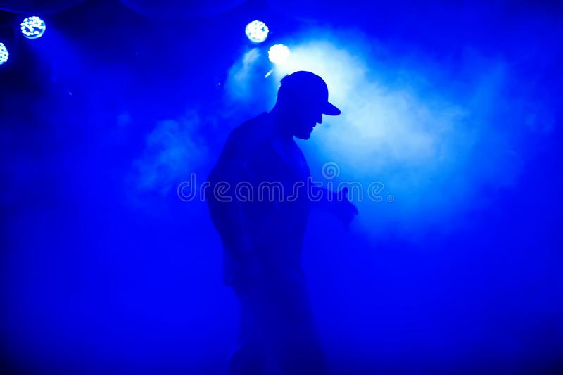 Silhouette of lead in cap of rocker on stage in smoke in nightclub at concert royalty free stock photo
