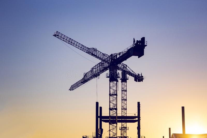 Silhouette of lifting tower construction crane. On the sunset stock image