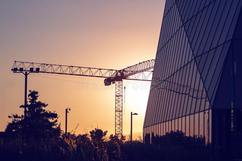 Silhouette of lifting tower construction crane. On the sunset royalty free stock image