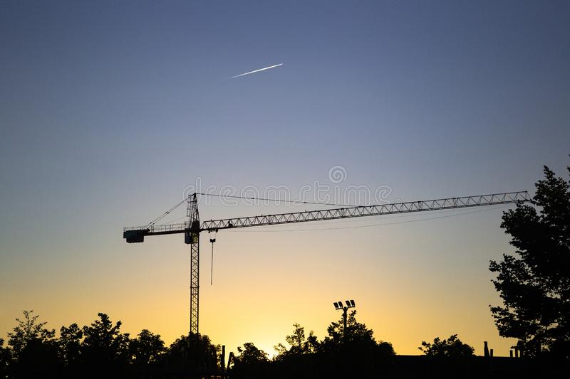 Silhouette of lifting tower construction crane. On the sunset stock photo
