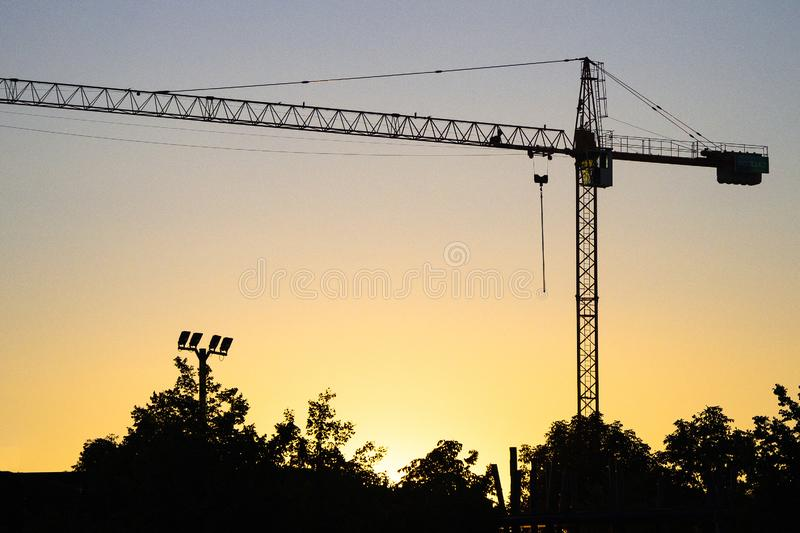 Silhouette of lifting tower construction crane. On the sunset royalty free stock photography