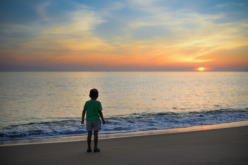 silhouette of little boy standing alone on stock image