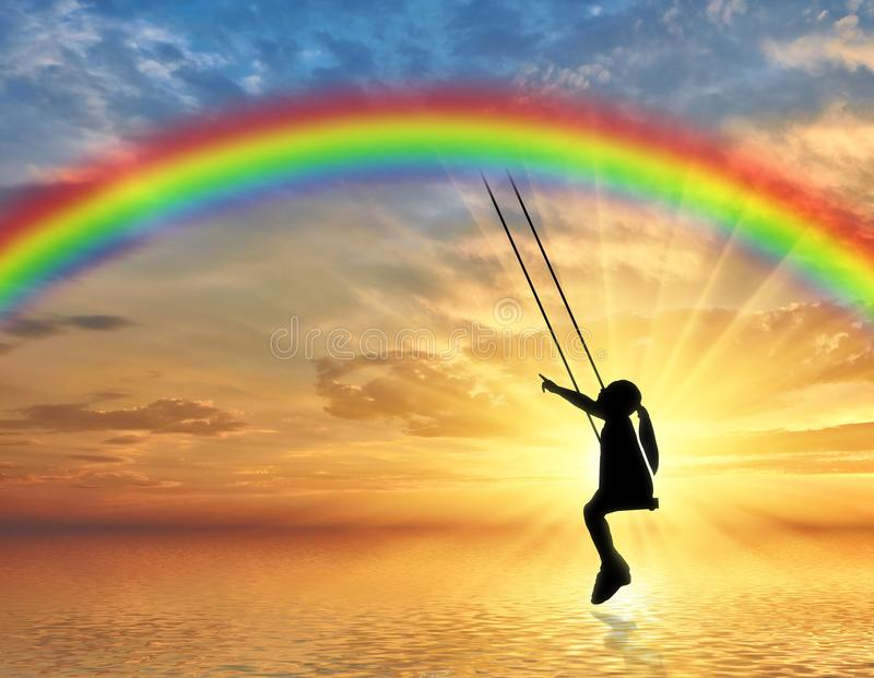 Silhouette, little girl child on a swing rainbow over the sea. royalty free stock photos