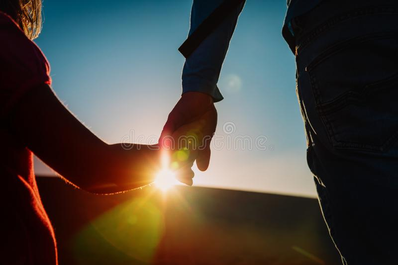 Silhouette of little girl and dad holding hands at sunset, parenting royalty free stock photo