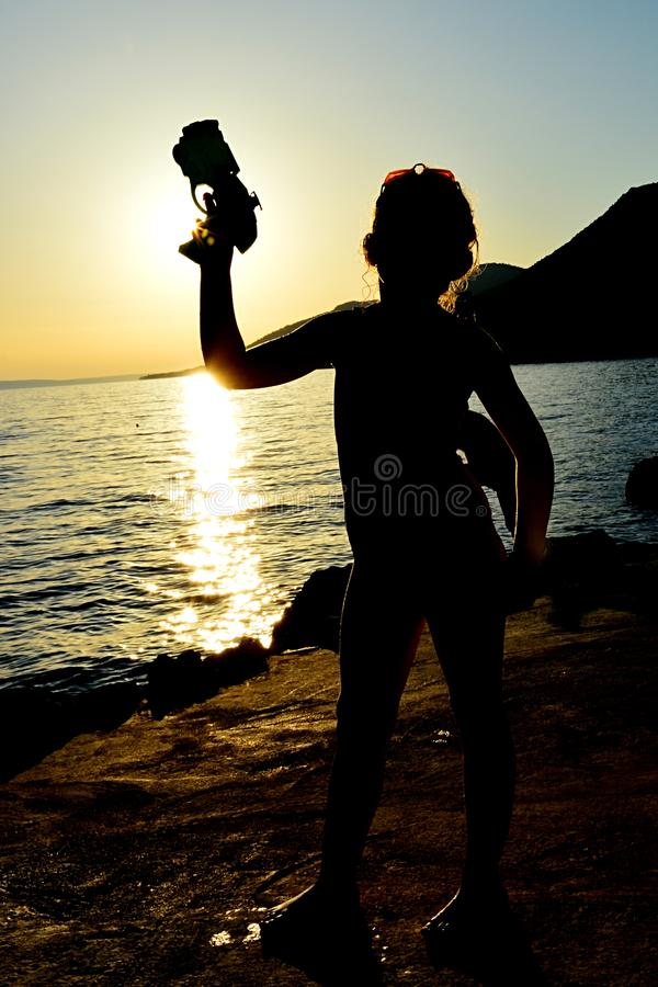 Silhouette of little girl with futuristic cyberpunk water pistol raised in left hand on rocky shore of Croatia. Silhouette of little girl with futuristic royalty free stock images