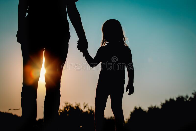 Silhouette of little girl holding parent hand at sunset stock photography