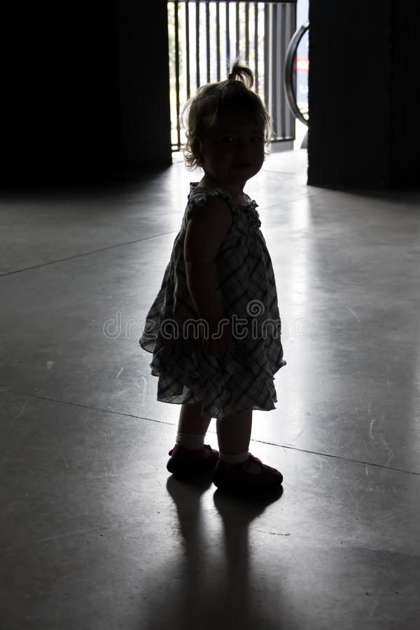 Silhouette of a little girl left by her parents in a shelter. Concept: abandoned and lost children, orphans and loneliness. Silhouette of a little girl left by stock image