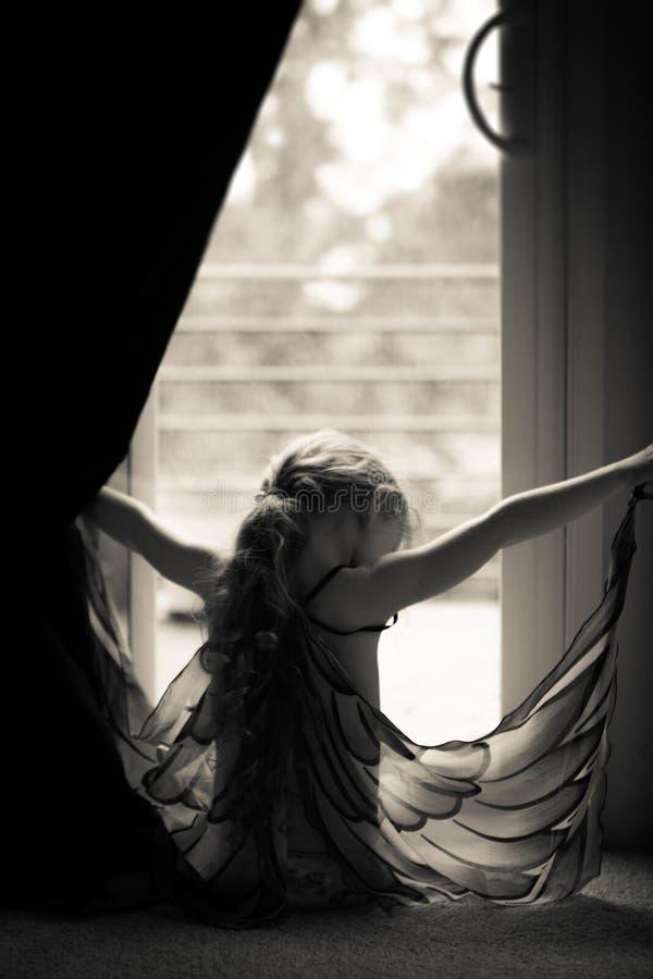 silhouette of little girl wearingg butterfly wings stock photos