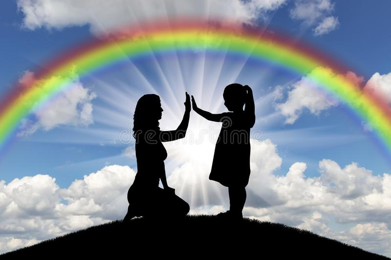 Silhouette, little happy girl child with mom on the hill and rainbow in the sky stock photo