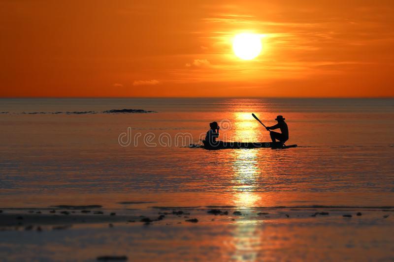 Silhouette of Local fishermen rowing small boats along the coast by the beach red sky sunset royalty free stock image