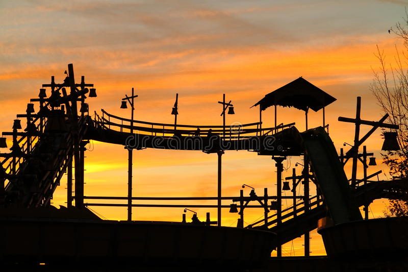 Log flume ride vintage by orange sunset sky scenery. An old-fashioned fairground ride set against a golden colored sky by sunset. Two persons boating on the top royalty free stock photos