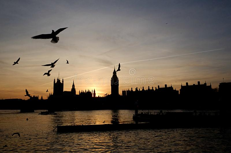 Silhouette of London skyline over the river of Thames stock images