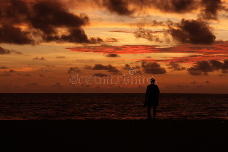 Silhouette of a lone man on a beach at dusk stock photos