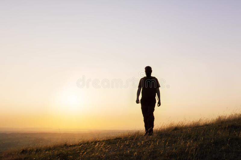 A silhouette of a lone man with a rucksack walking towards the camera on a hill with the sun setting across the landscape on a sum stock image