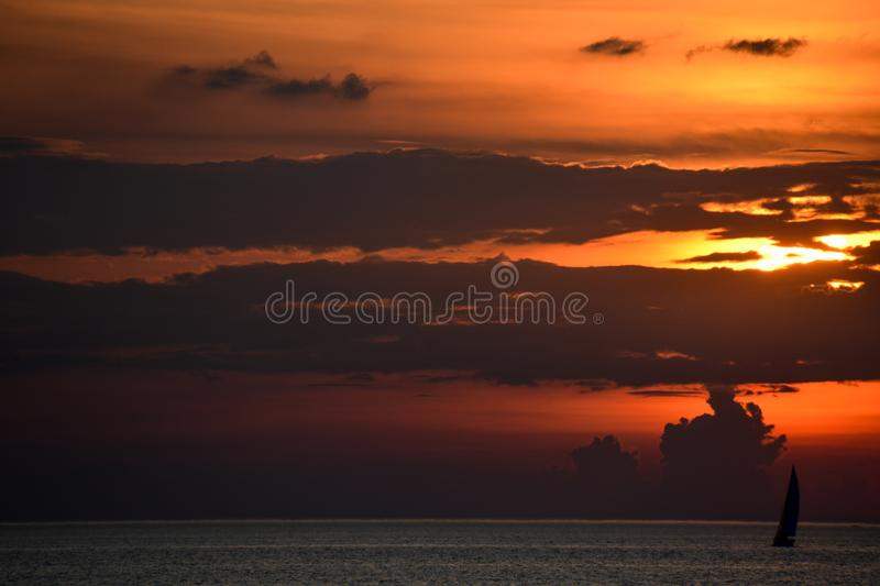 Silhouette of lone sailboat on lake erie at sunset royalty free stock images