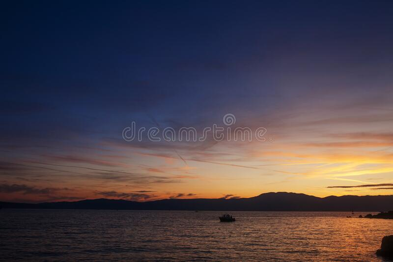 Silhouette of lonely boat in the sunset with dramatic sky. High seas sunset with a fishing ship on the horizon royalty free stock image
