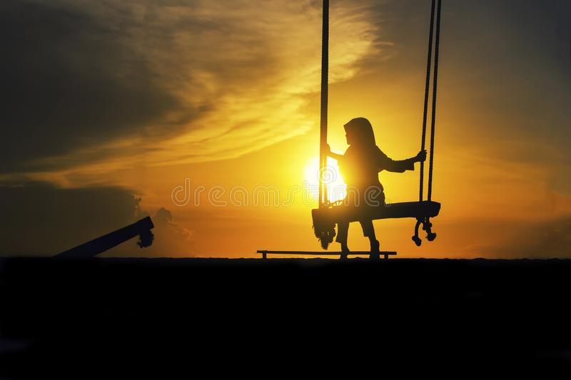 Silhouette of lonely girl with hijab on a swing with magical sunrise royalty free stock images