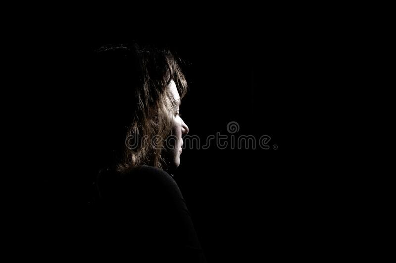 Silhouette a lonely and sad girl on a black background stock image