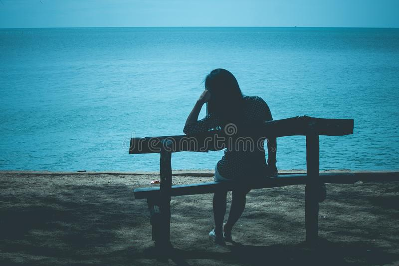 Silhouette of lonely woman sitting on wooden bench on the beach and looking to blue sea. royalty free stock photography