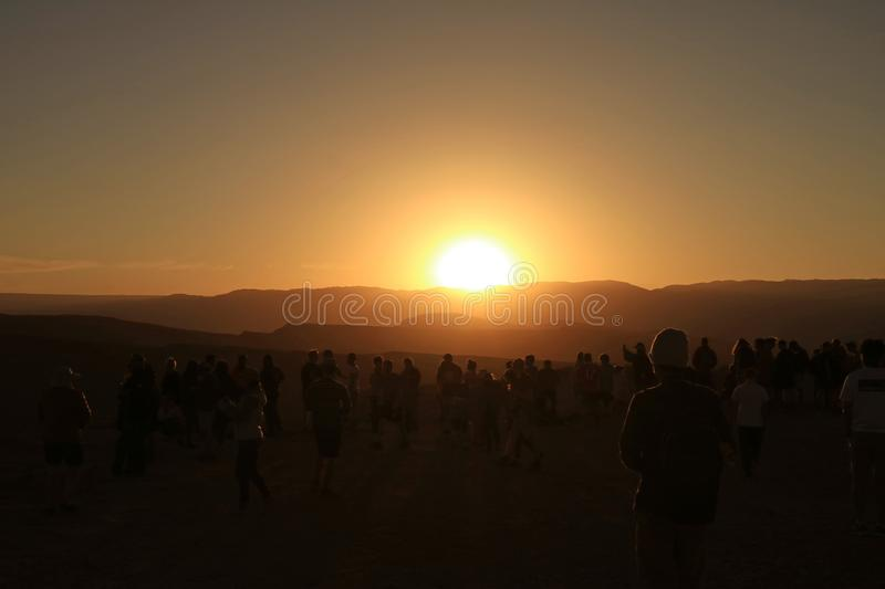 Silhouette of a lot of people watching the incredible sunset at Valle de la Luna or Moon Valley in Atacama Desert, Chile stock photography