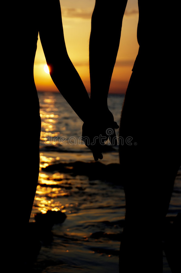 Silhouette in love on sunset. Silhouette the man and woman on sunset royalty free stock images