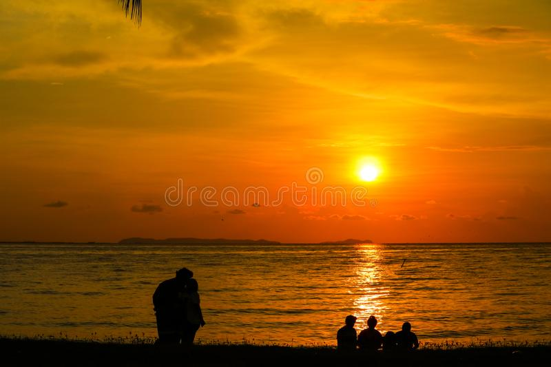 silhouette of lover standing and family sitting look at sunset stock image