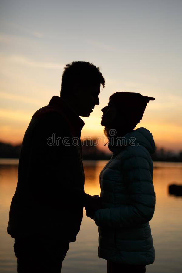 Silhouette of lovers couple on sunset by the lake. Sun between people profiles. Dusk sky, water on background. Passion in love con stock photo