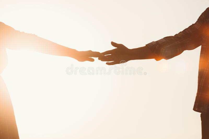 Silhouette of lovers hands stretching towards each other royalty free stock image