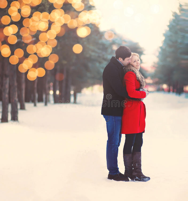 Silhouette of loving couple embracing in warm winter day. With lights bokeh, vintage colors royalty free stock images