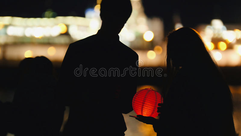 Silhouette loving couple at festival of floating Lanterns near river at night. Telephoto royalty free stock images