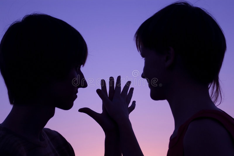 Silhouette of loving couple keeping hands together stock images