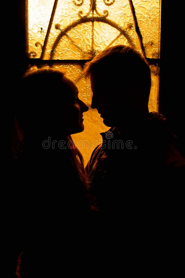 Silhouette of a loving couple. Lovers embrace in the dark. Silhouette of a guy with a girl. Photo portrait of lovers close up. Dra. Matic photo portrait royalty free stock photo