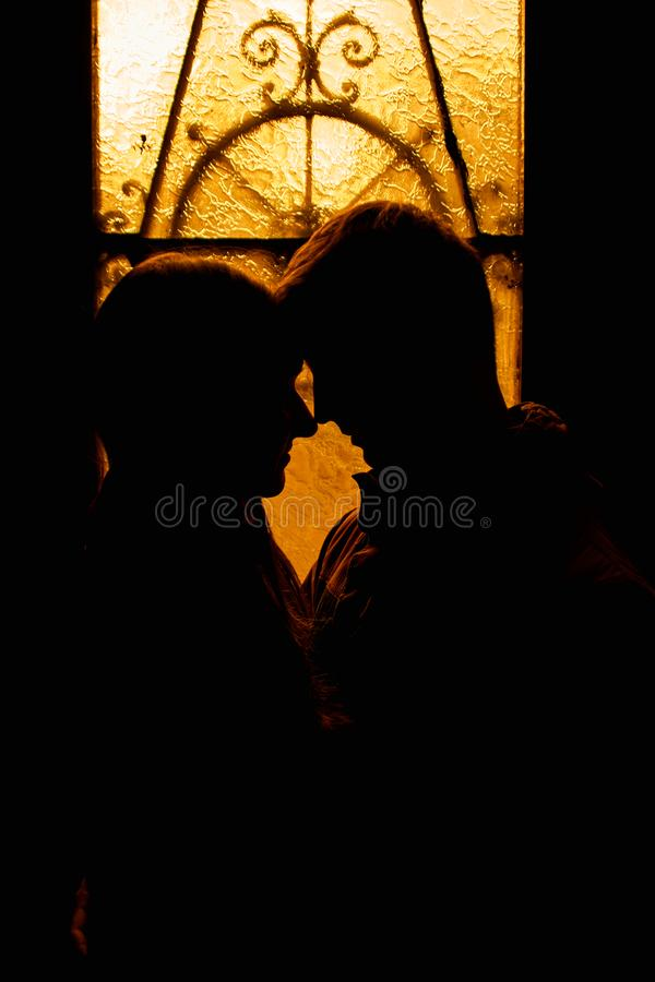 Silhouette of a loving couple. Lovers embrace in the dark. Silhouette of a guy with a girl. Photo portrait of lovers close up. Dra. Matic photo portrait royalty free stock photos