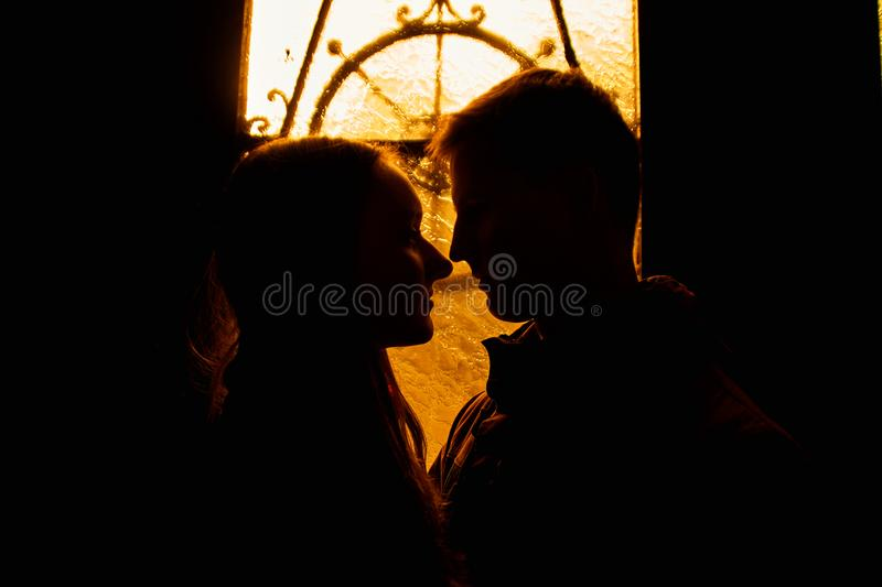 Silhouette of a loving couple. Lovers embrace in the dark. Silhouette of a guy with a girl. Photo portrait of lovers close up. Dra. Matic photo portrait stock photos