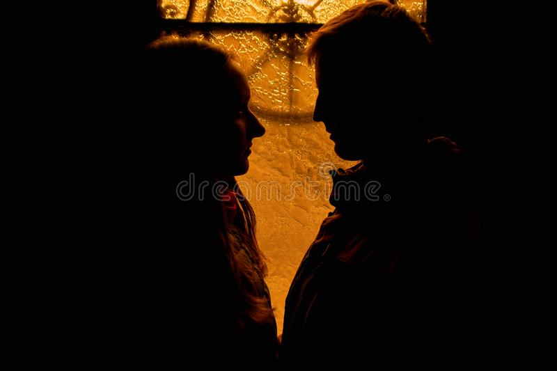 Silhouette of a loving couple. Lovers embrace in the dark. Silhouette of a guy with a girl. Photo portrait of lovers close up. Dra. Matic photo portrait royalty free stock photography