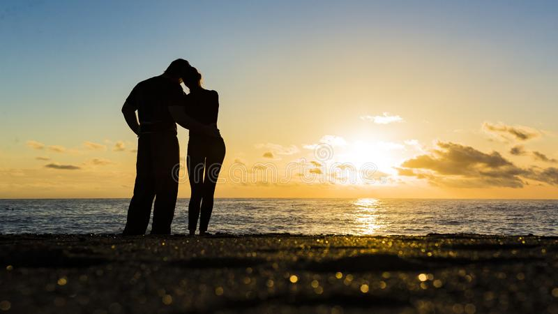 Silhouette of loving couple standing riverside and beautiful sunset background. royalty free stock photography