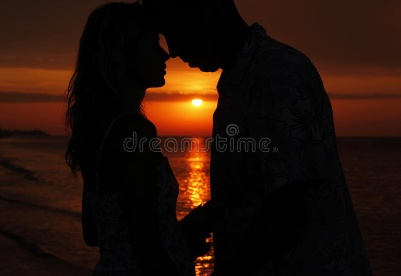 Silhouette of a loving couple at sunset royalty free stock photography