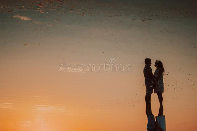 Silhouette of a loving couple at sunset near the sea royalty free stock photo
