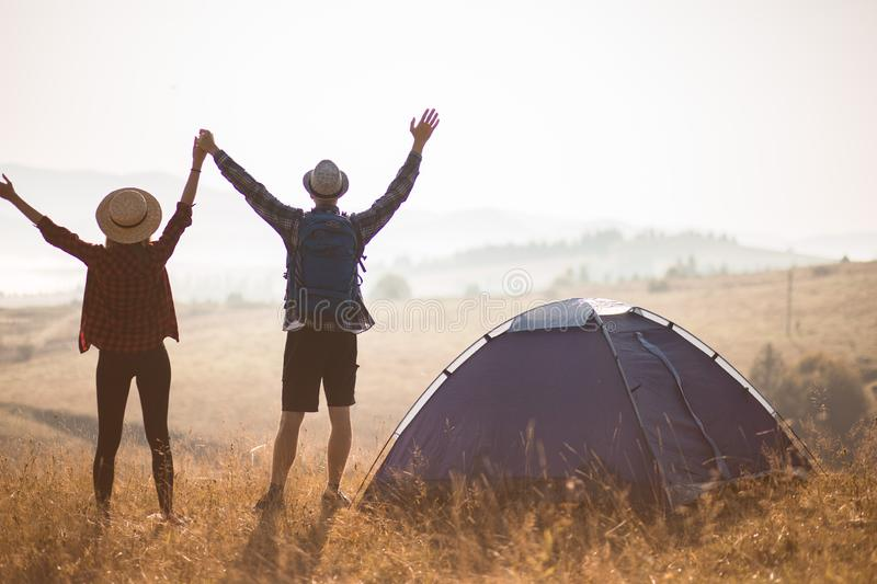 Silhouette of loving couple travel relax camping in autumn holiday. On top of moutain. Enjoy sunrise with hands up. stock photography