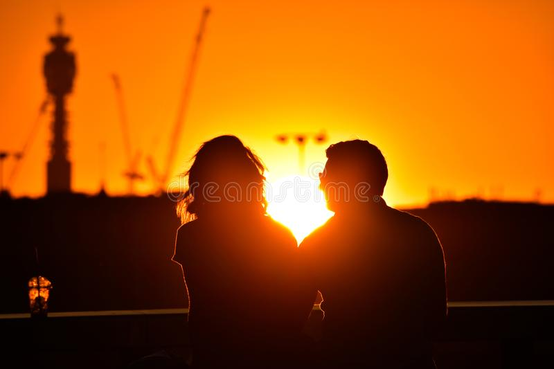 Silhouette of loving couple watching beautiful bright romantic sunset royalty free stock image